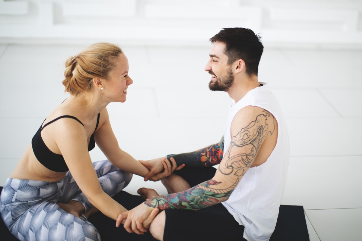 Young woman and man talking after yoga classes
