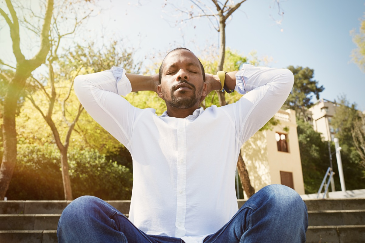 Man taking a deep breath on a park bench