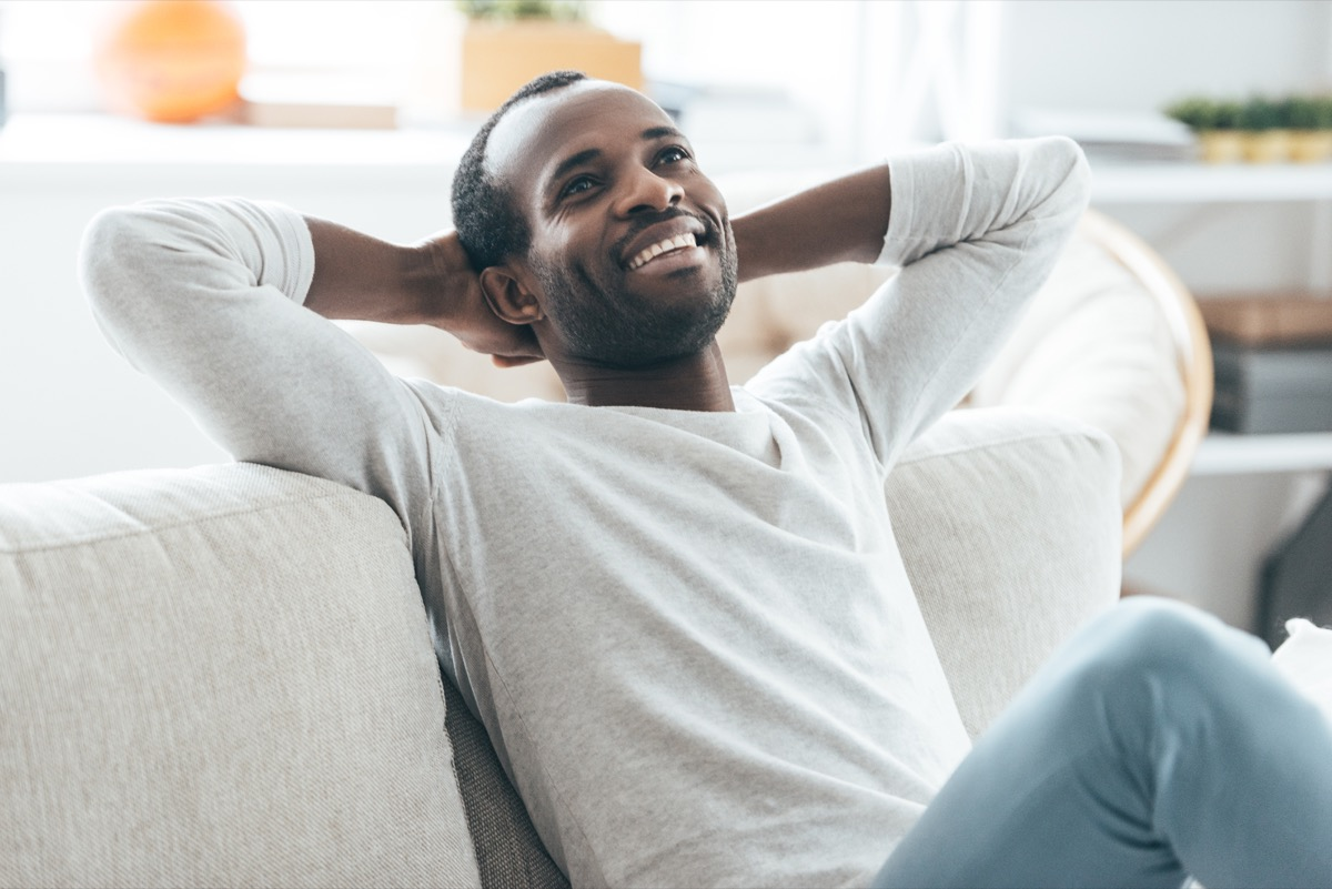 Happy man thinking and smiling on the couch