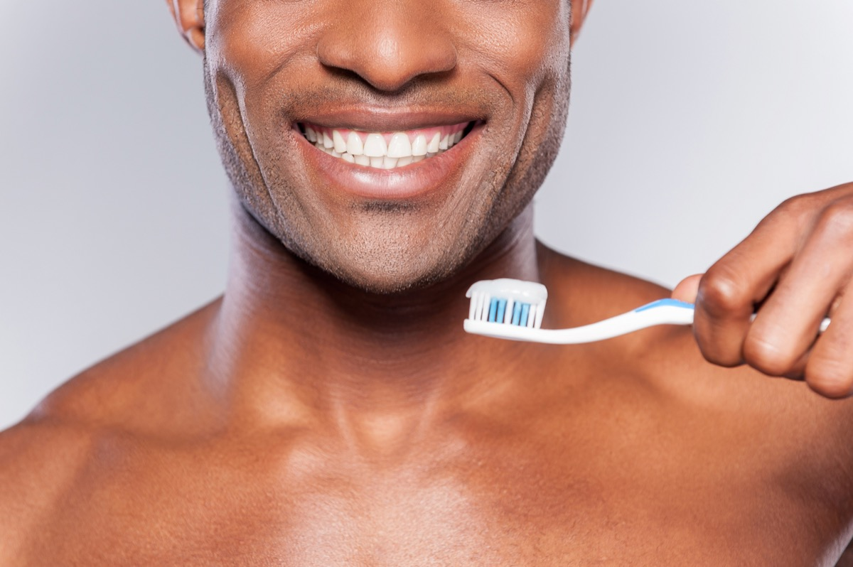 Man holding a toothbrush with toothpaste on it while smiling