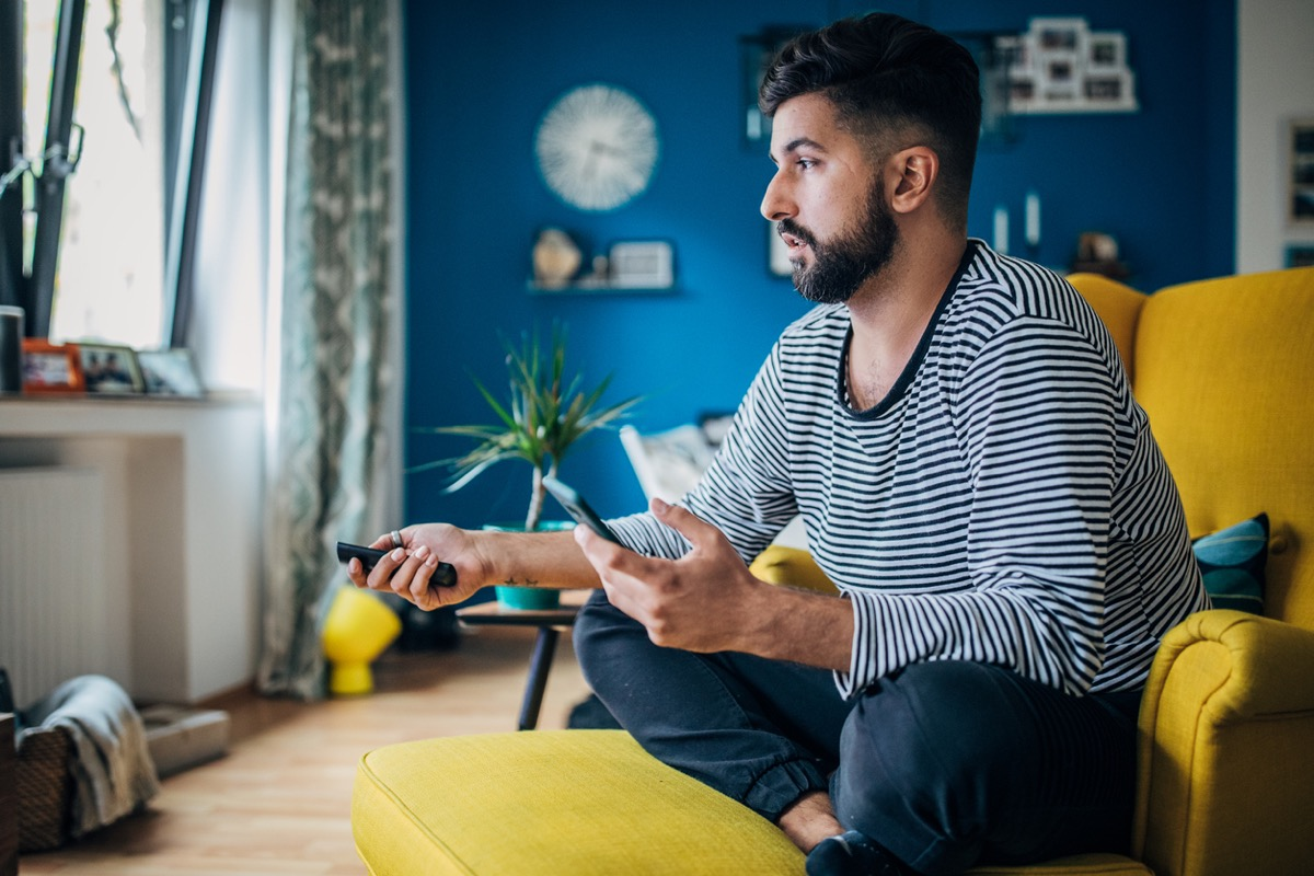 Man sitting home in his armchair, using phone and changing channels