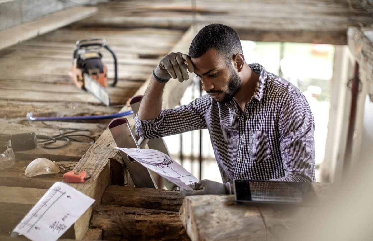 young black man looking at instructions as he renovates attic