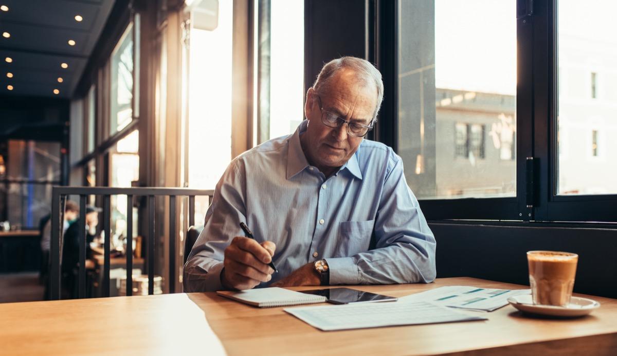 Mature businessman making notes while sitting at cafe. Senior man at modern coffee shop working.