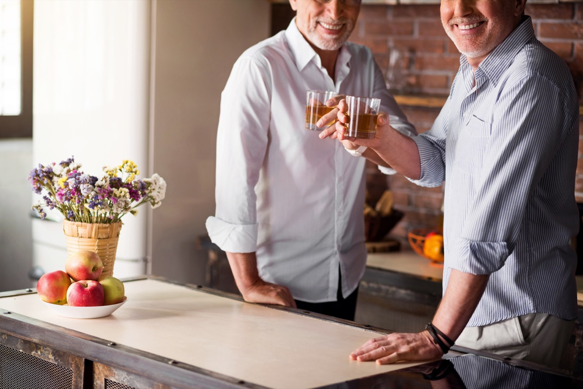 Middle-aged men smiling at the camera while having their whiskey