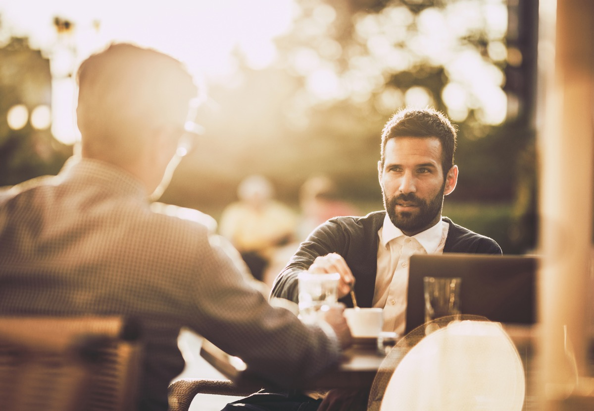 businessman communicating with his colleague while having a coffee break in a street cafe at sunset.