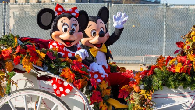 mickey and minnie in an open carriage during a disneyland parade
