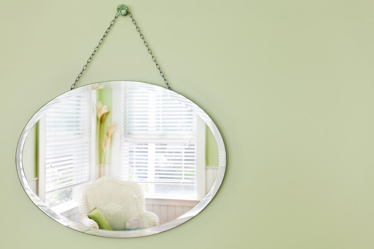 Hanging mirror reflecting windows and sunlight