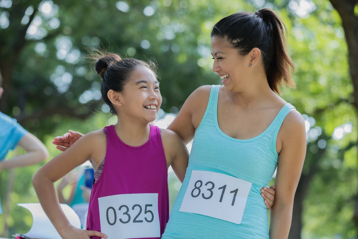 Asian mother and daughter pose together during a race in a public park on a sunny day.