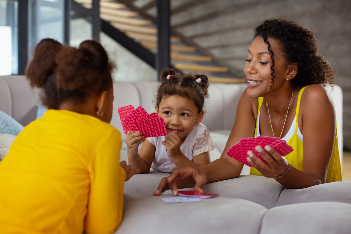 mom playing cards with daughters on couch cushions