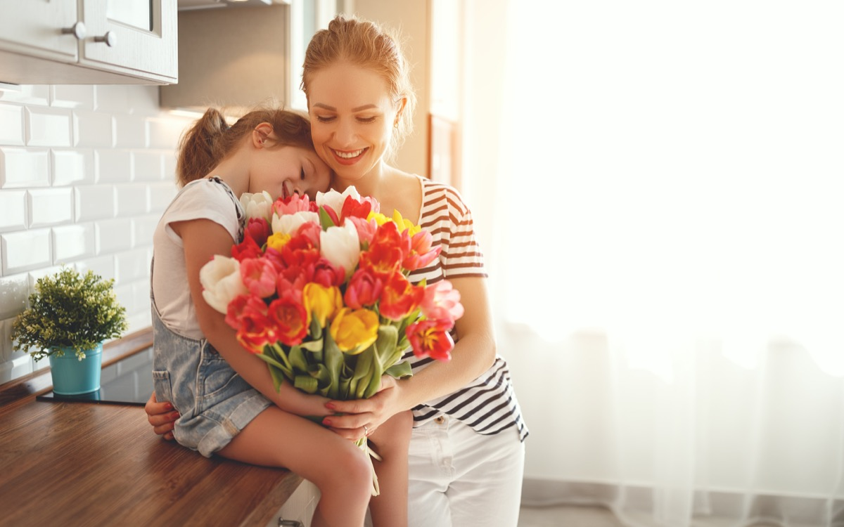 Mother and daughter holding a bouquet of flowers in the kitchen smiling