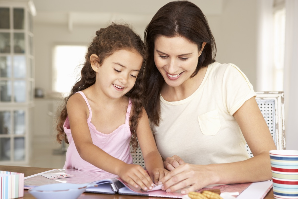 Mother and daughter creating a scrapbook together