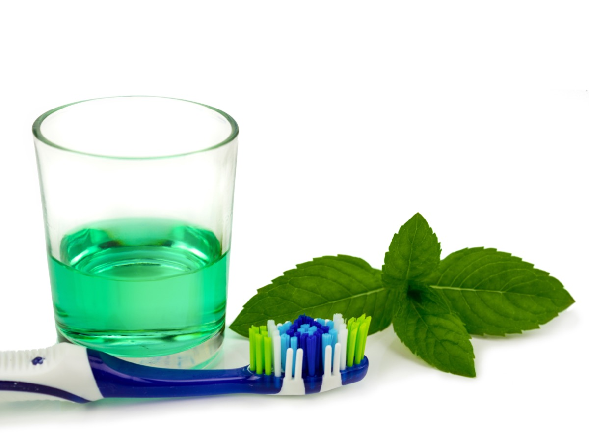 A cup of mouthwash and a toothbrush