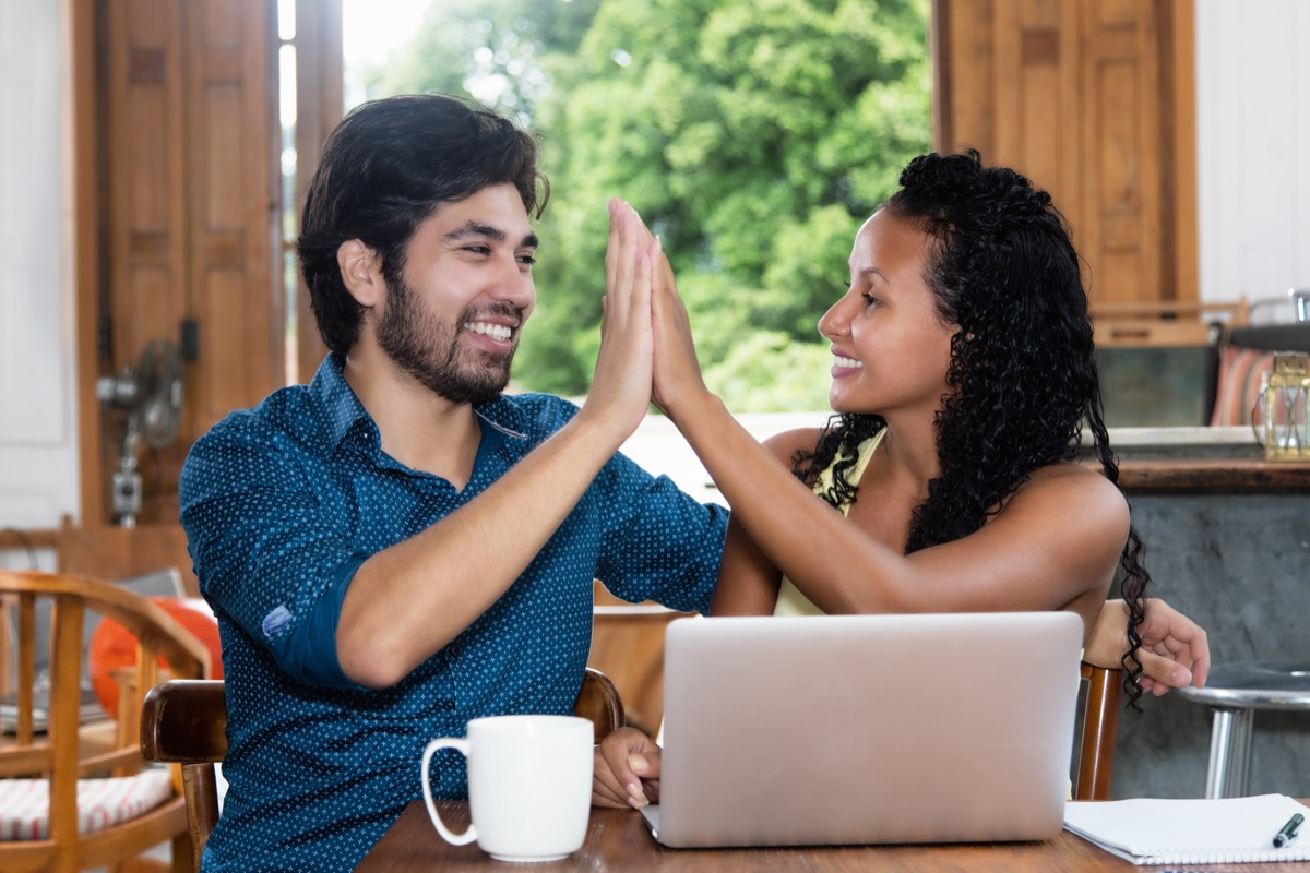 Multicultural couple high-fiving using computer