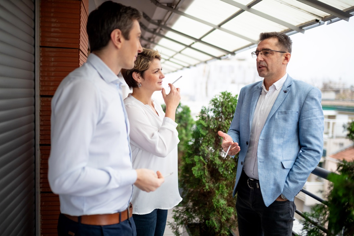 group of business people smoking outdoors on a break, talking to each other