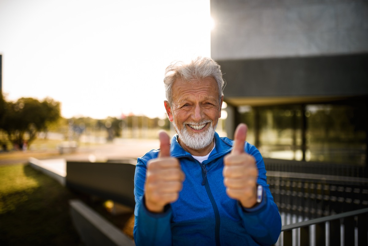 portrait of a smiling senior man showing his thumbs up
