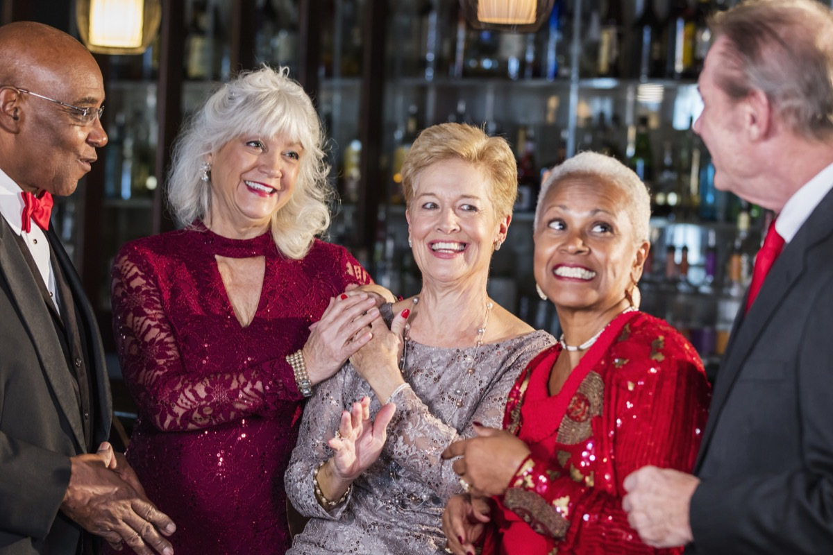 a multi-ethnic group of five seniors enjoying a night out, hanging out together at the bar counter of a restaurant, talking and laughing. They are well-dressed, wearing suits and dresses. The woman in the middle is in her 70s and her friends are in their 60s.