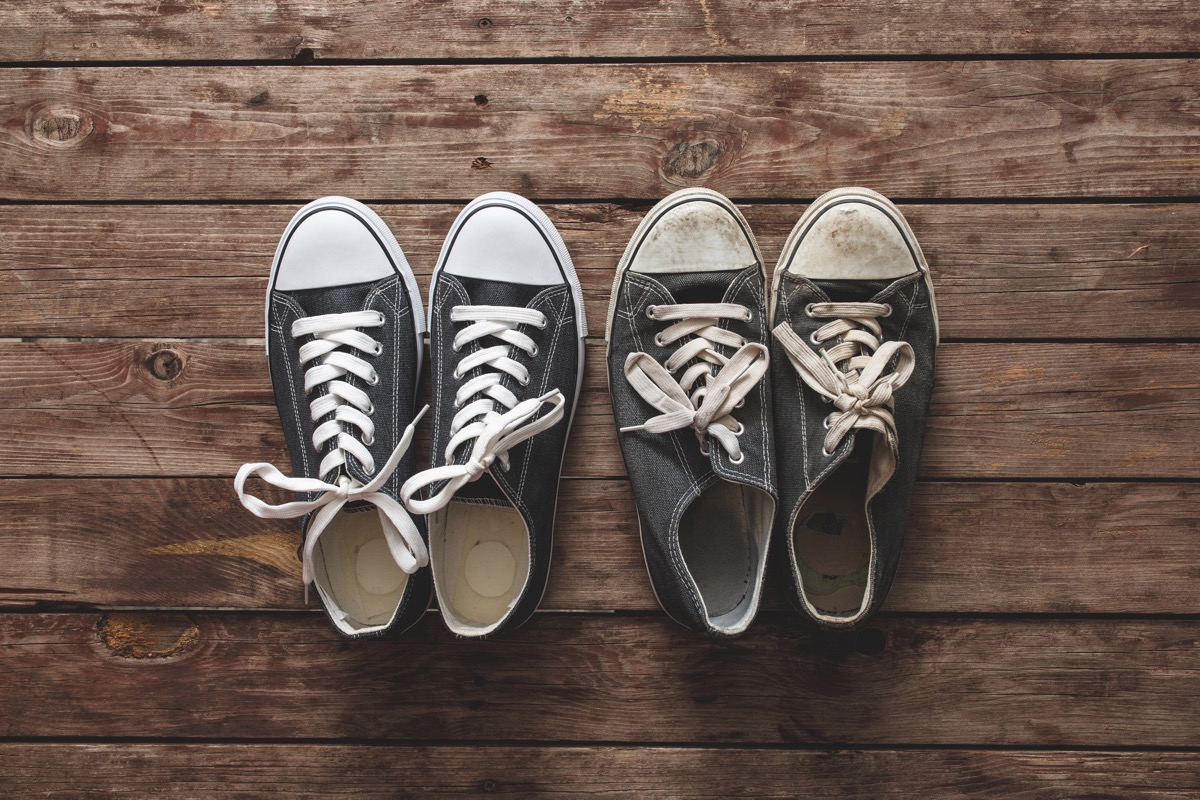 new and old sneakers on wooden background.