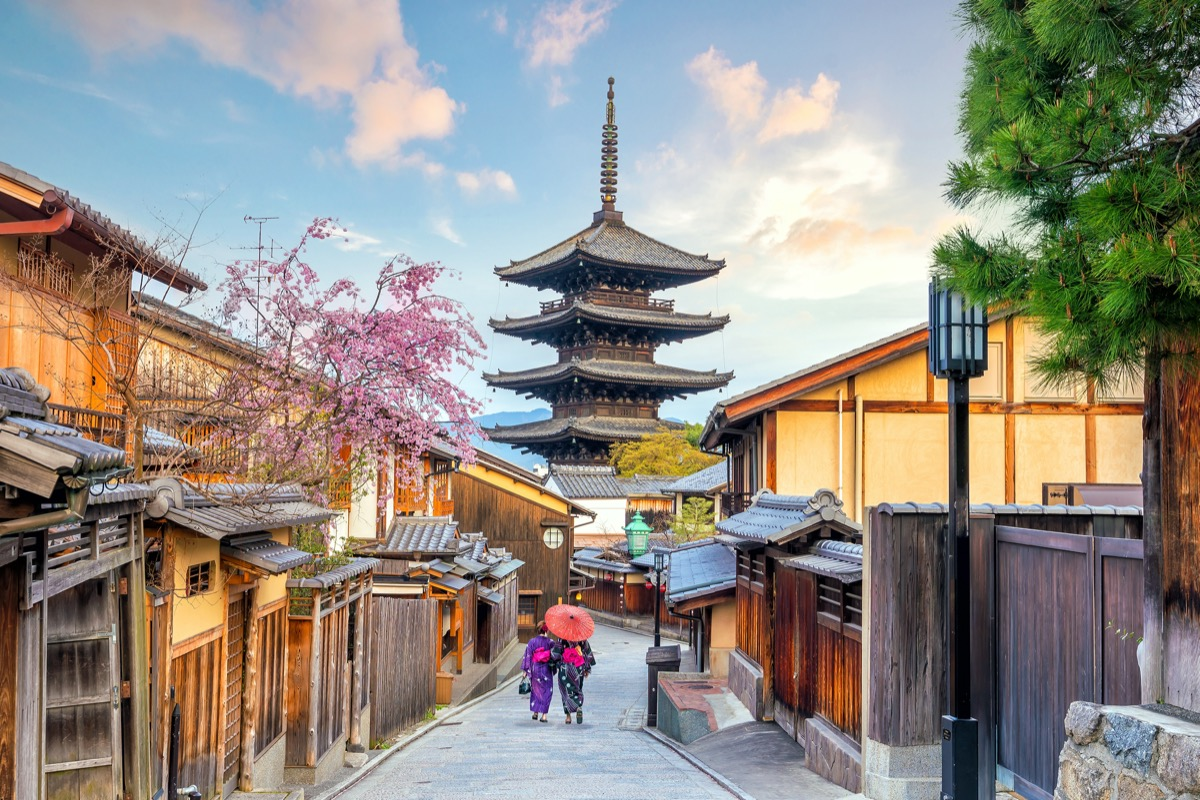old town kyoto with two women dressed in kimonos walking down the road