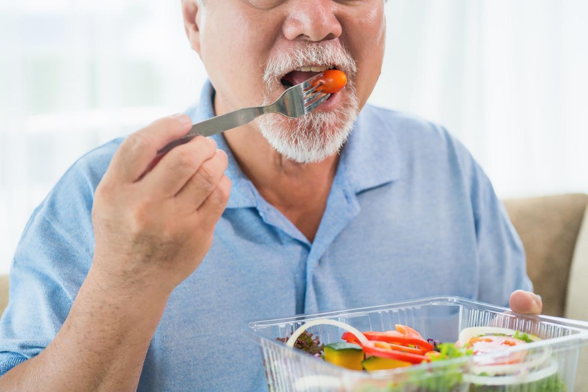 older asian man eating salad