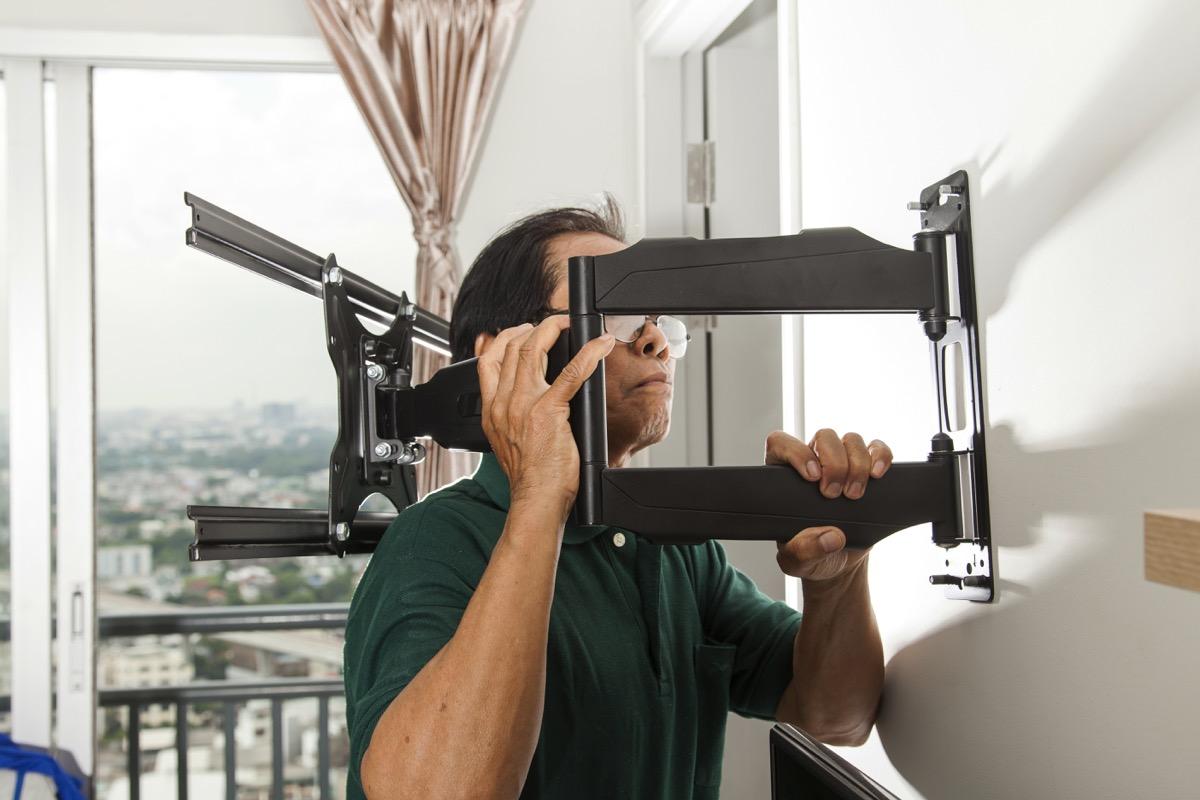 older asian man installing tv bracket on wall