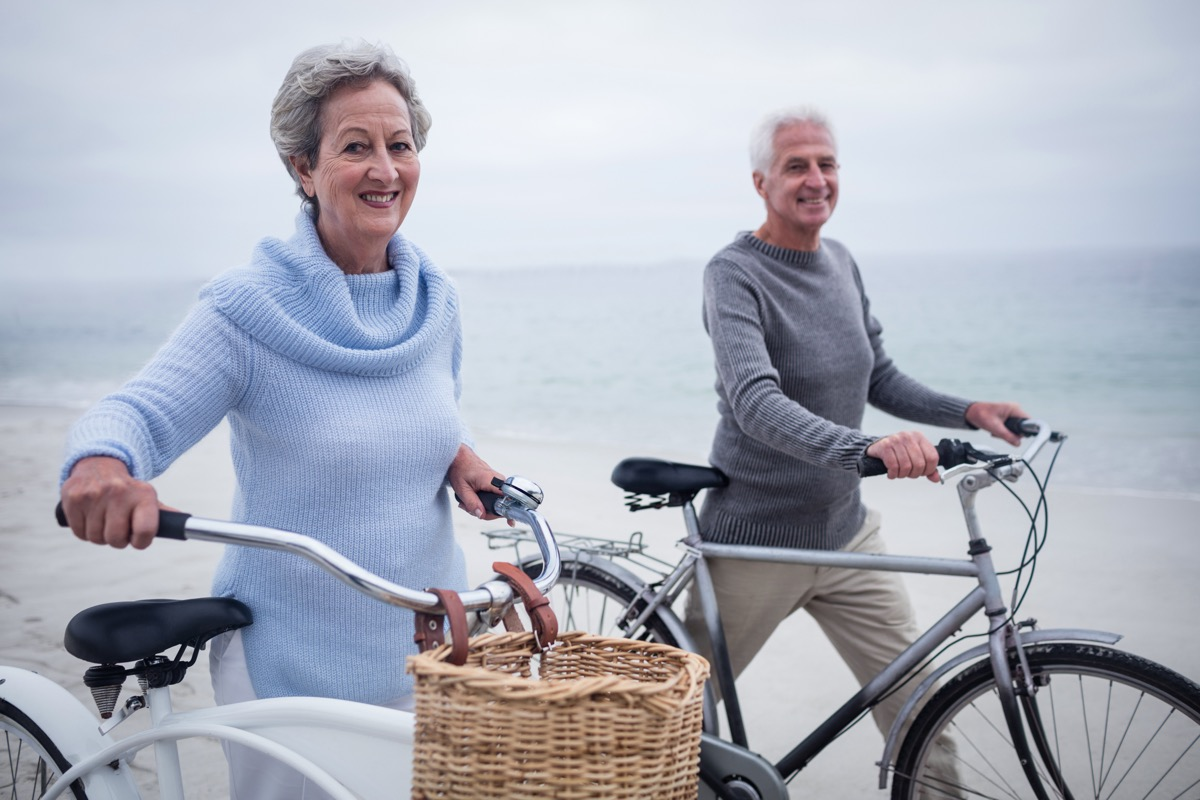 Older couple going for a bike ride on vacation near the beach