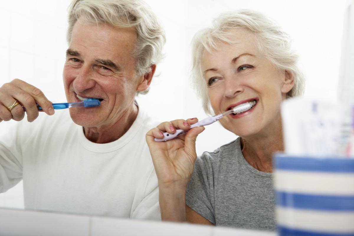 Older couple brushing their teeth in the bathroom