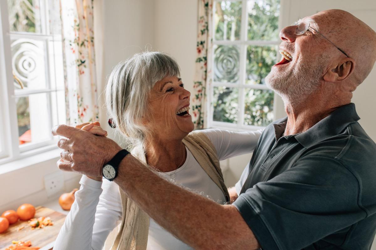 Senior man and woman dancing at home.