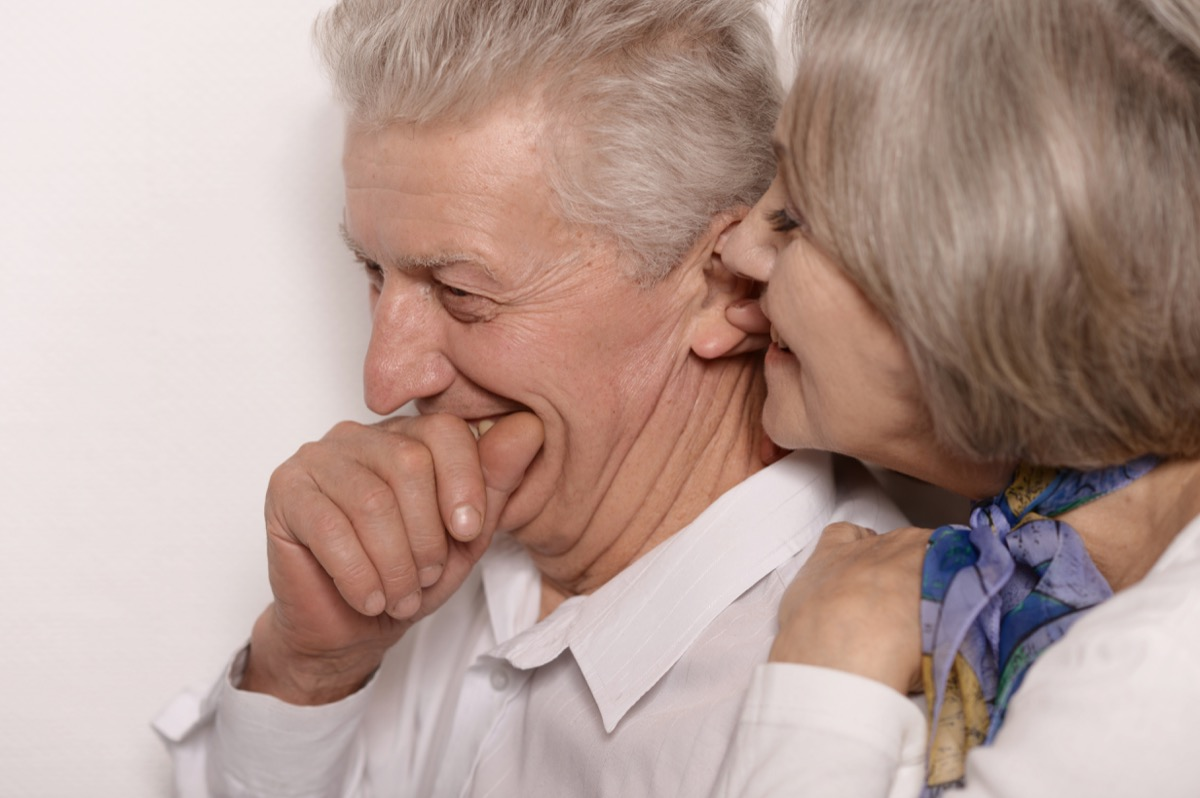 Older woman whispering into giggling old man's ear