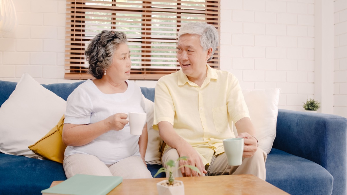 Older couple talking on the couch while drinking coffee or tea serious talk