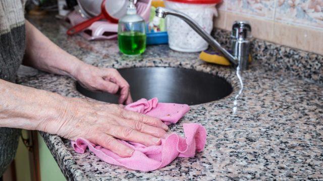 white hand cleaning granite counter