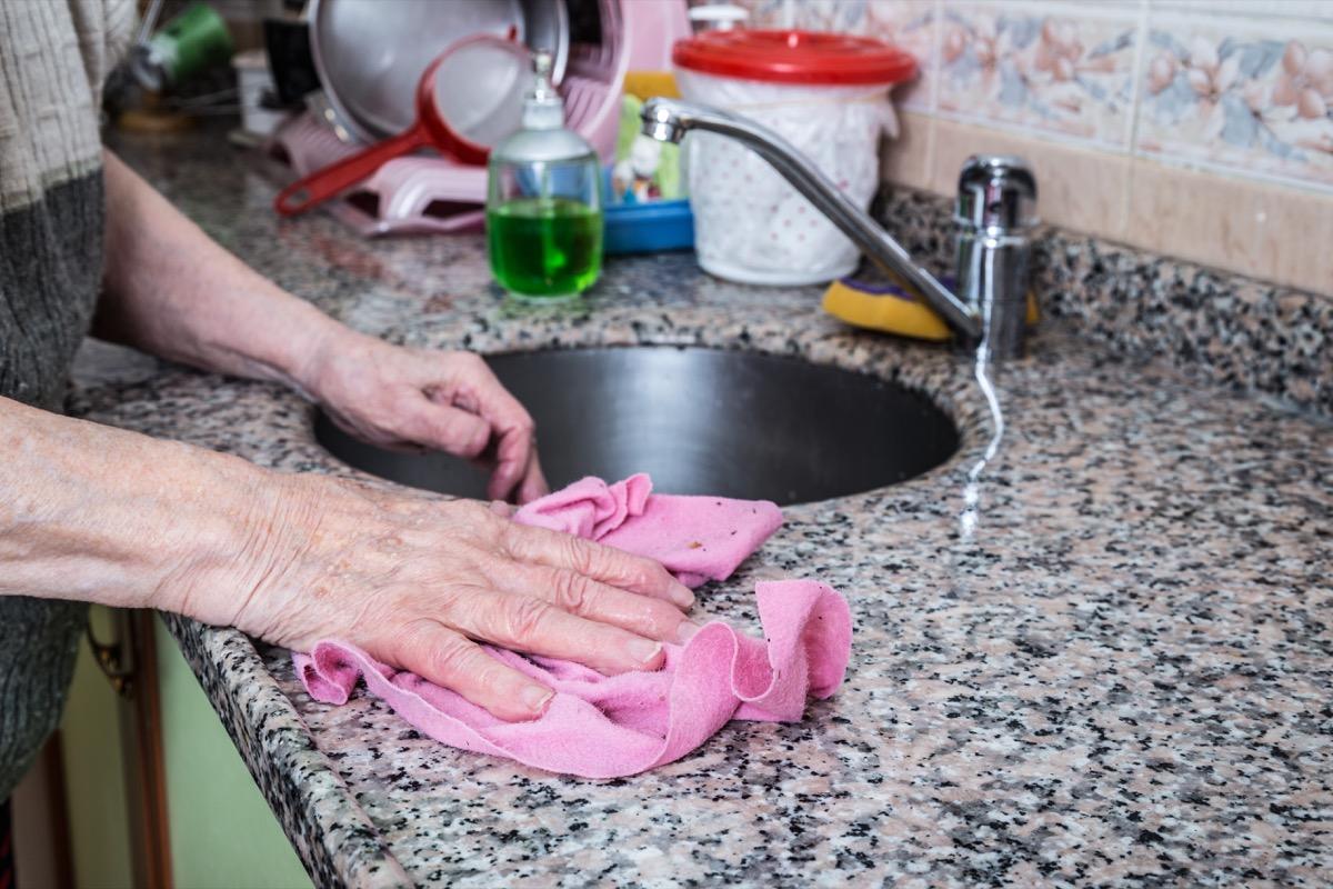 older man cleaning granite counter
