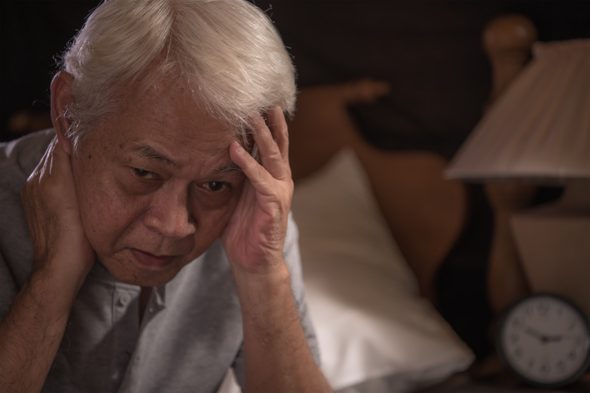 depressed senior person sitting in bed cannot sleep from insomnia