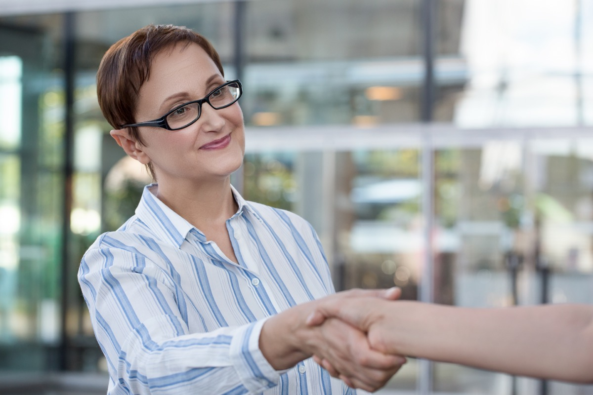 older woman in glasses shaking hands