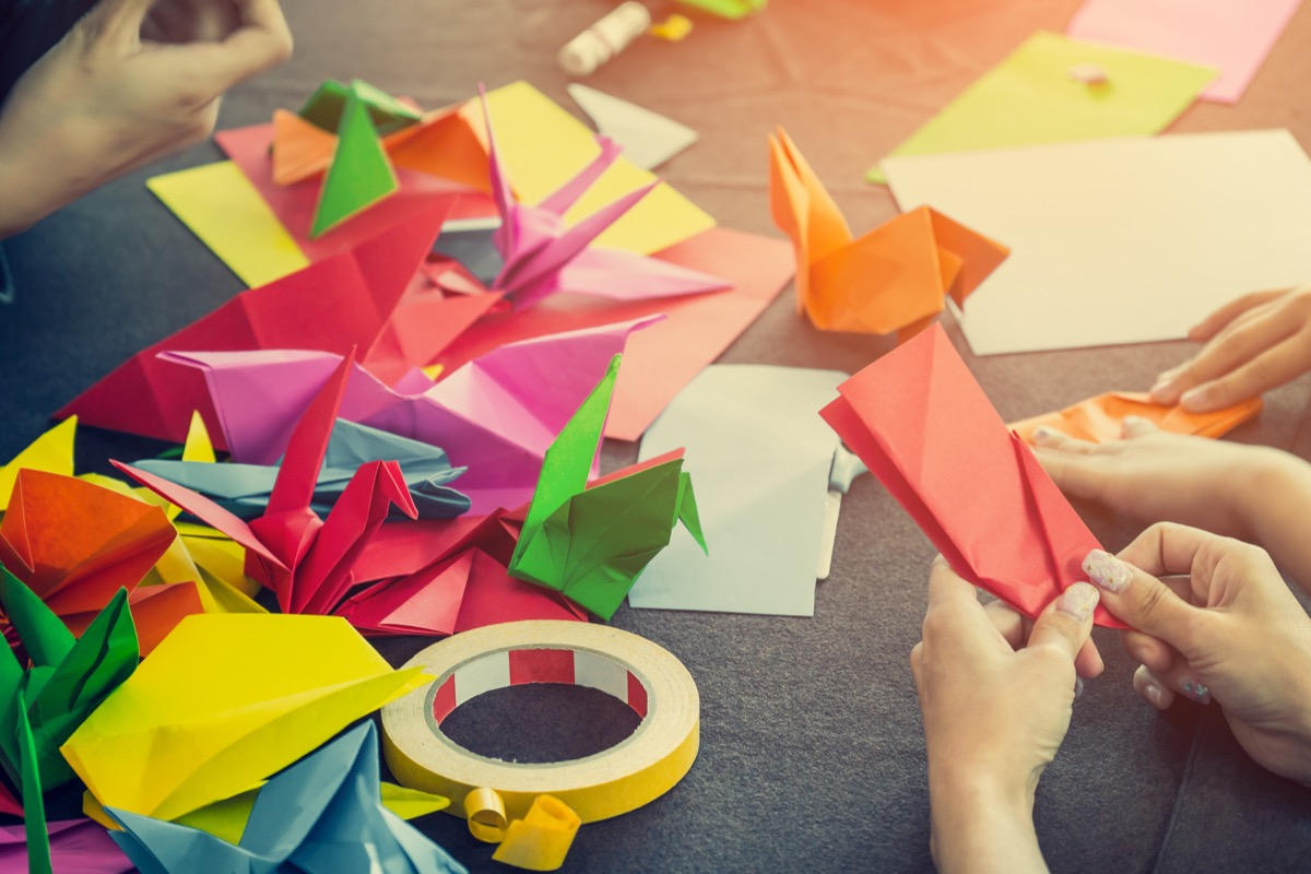 People making origami birds at table