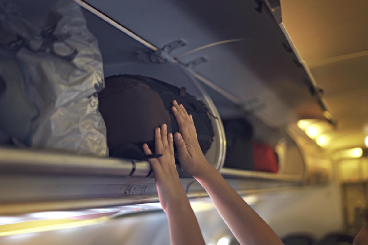 pushing carryon in overhead bin