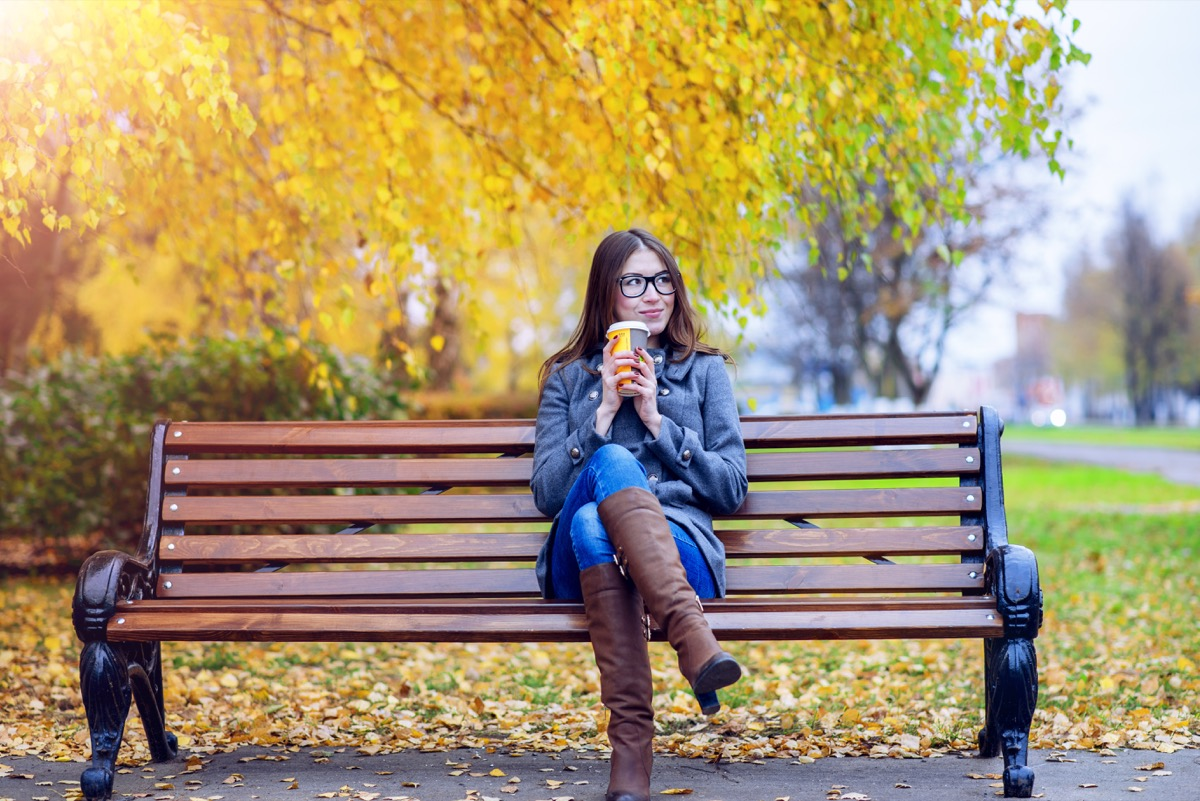 Woman drinking coffee on a park bench while people watching