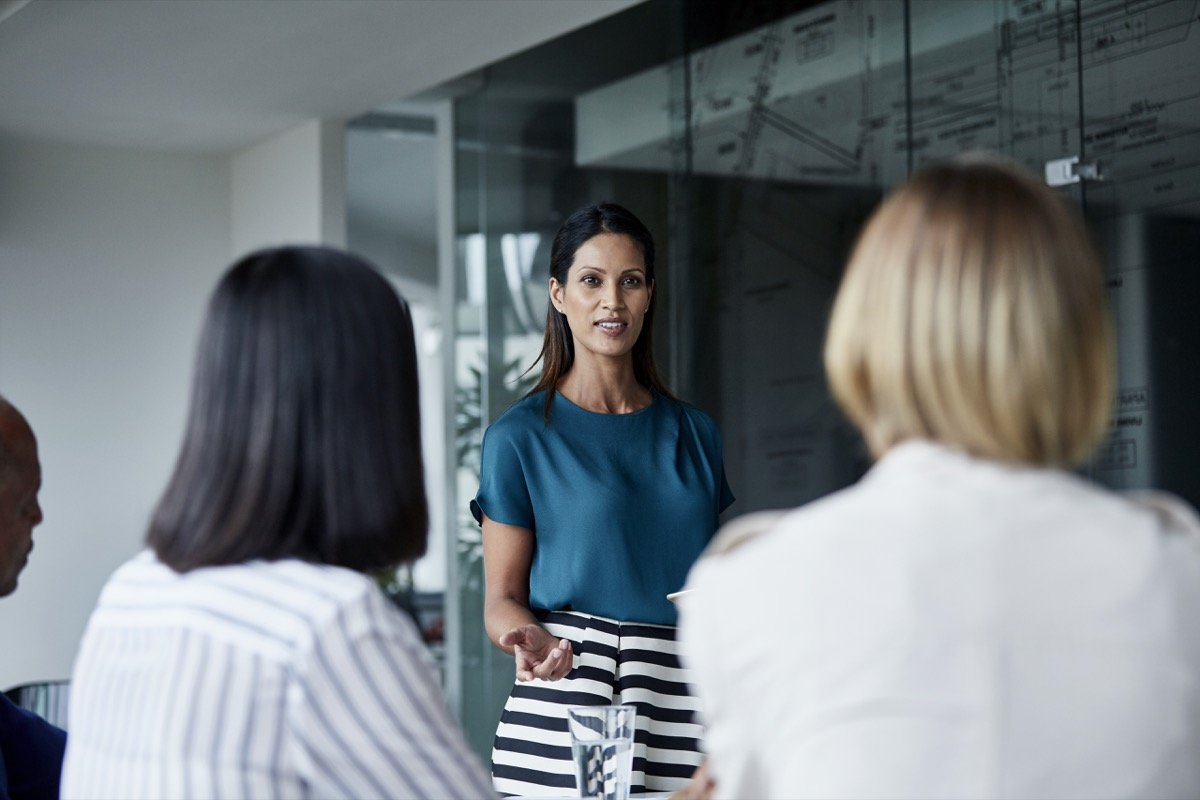 Young businesswoman discussing with team in meeting room