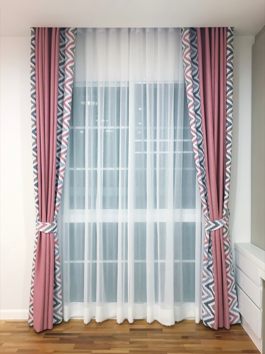 Pink and patterned blackout curtains on a window