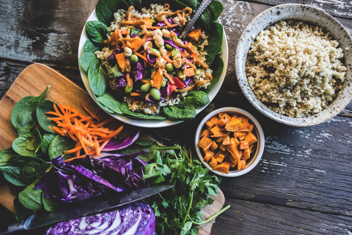 Colorful, rustic plant based meal of vegetables over coconut quinoa