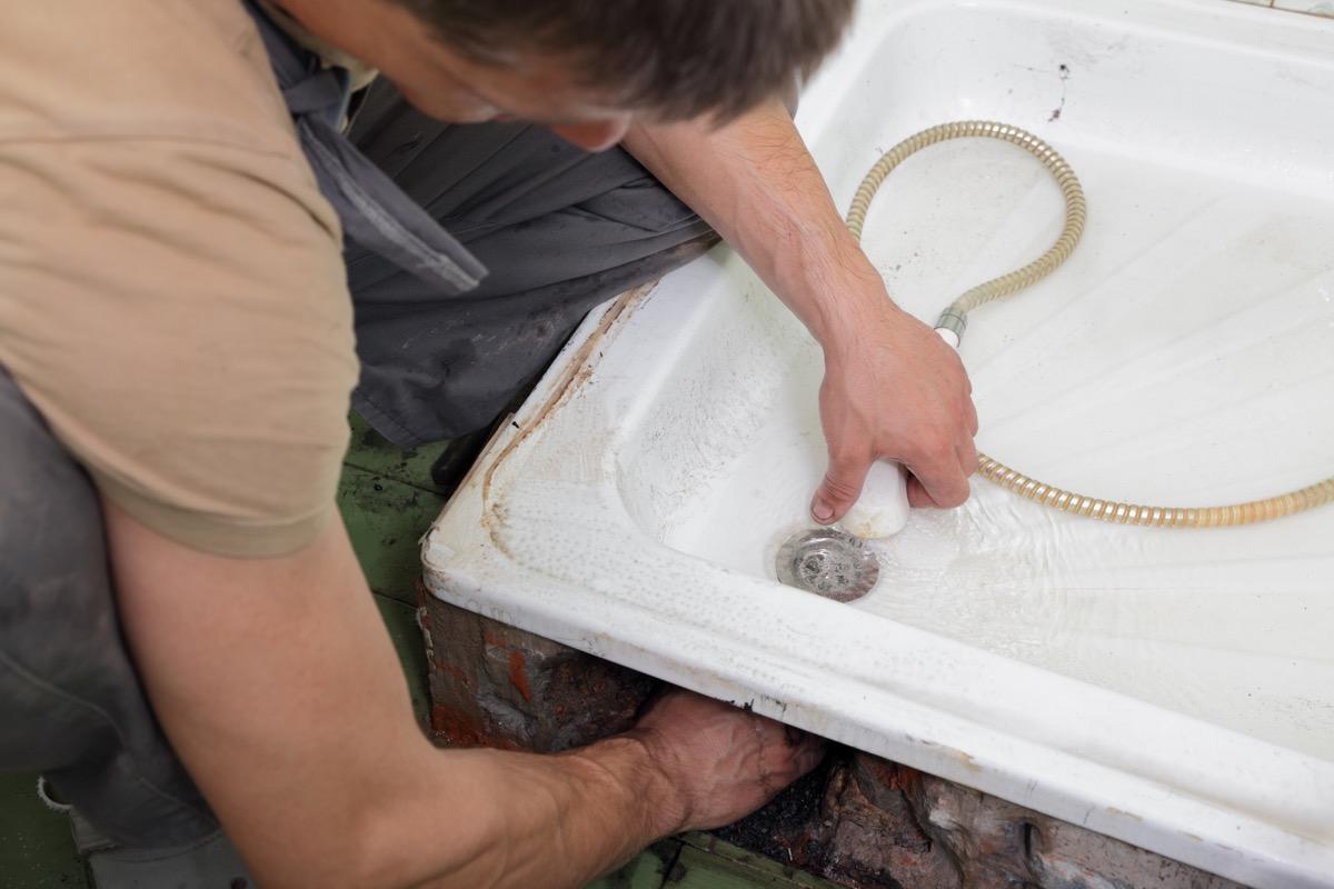 older white man repairing sink drain