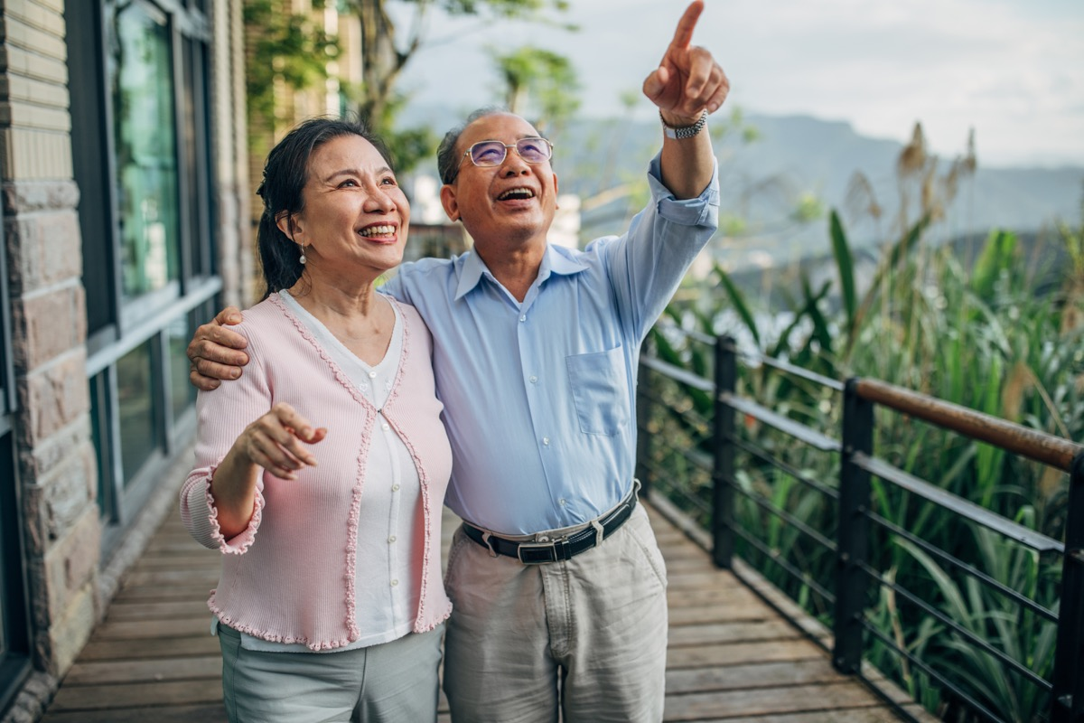 man and woman, senior married couple standing on terrace at home together.