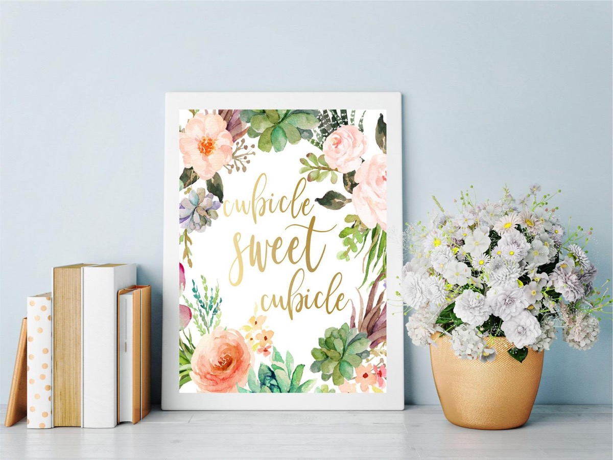 floral print in white frame next to flowers