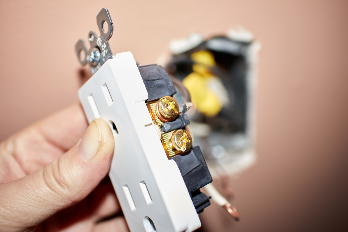 white hand removing electrical socket from wall