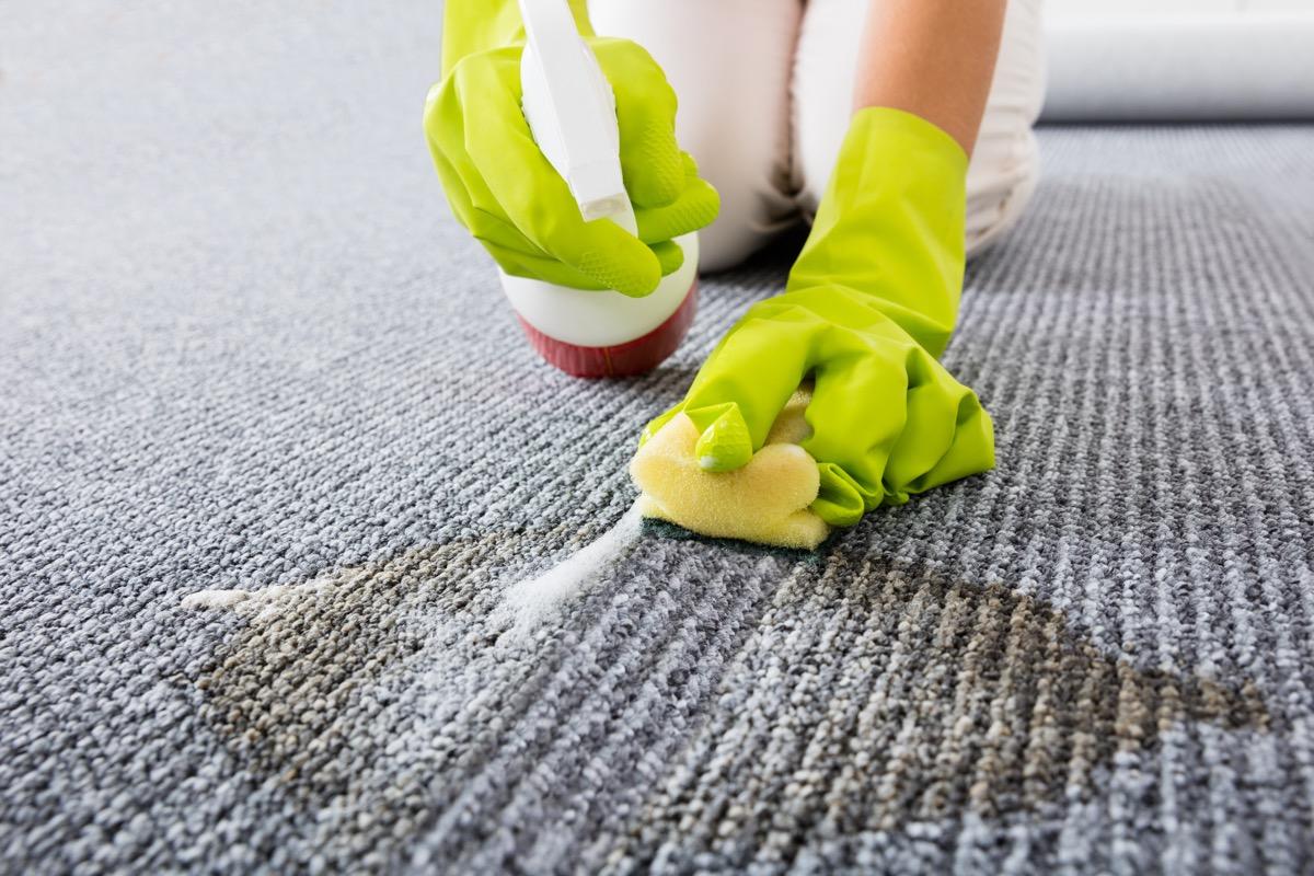 woman scrubbing carpet