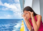 woman leans over cruise ship balcony seasick