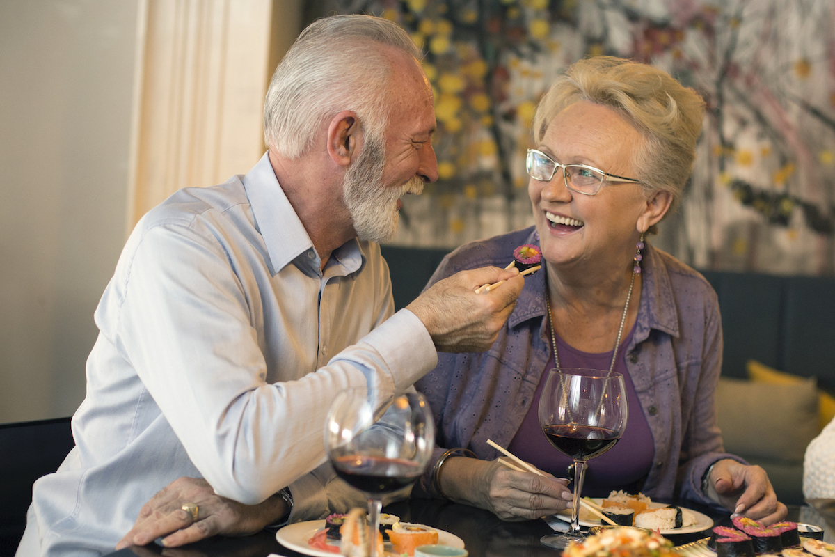 Senior couple in a restaurant, eating sushi.