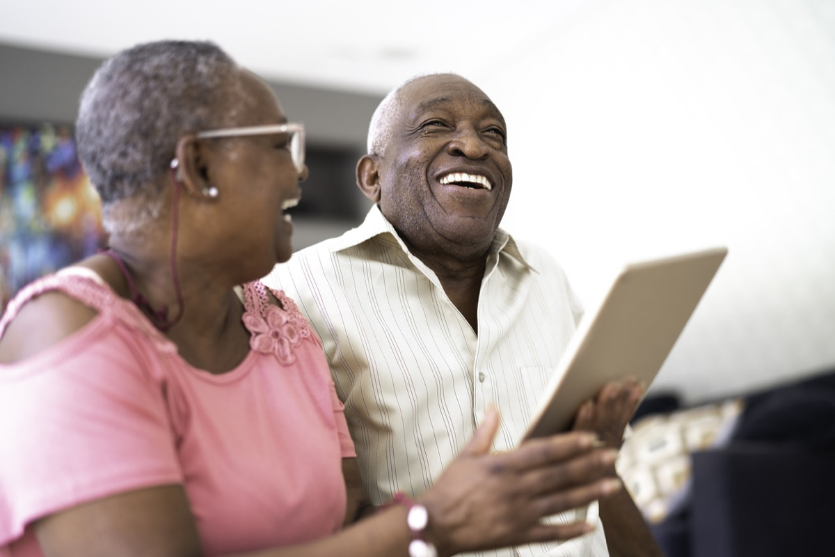 Senior black couple laughing while looking at tablet
