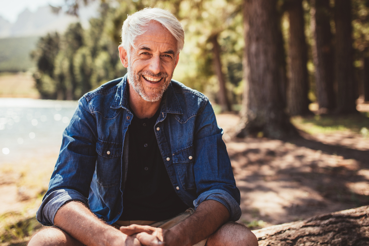 happy mature man sitting near a lake looking at camera and smiling