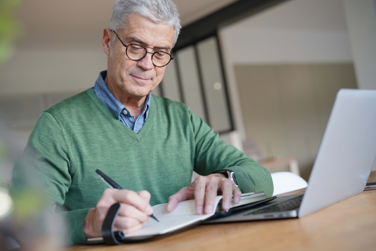 Older man writing down his thoughts in a journal or notebook