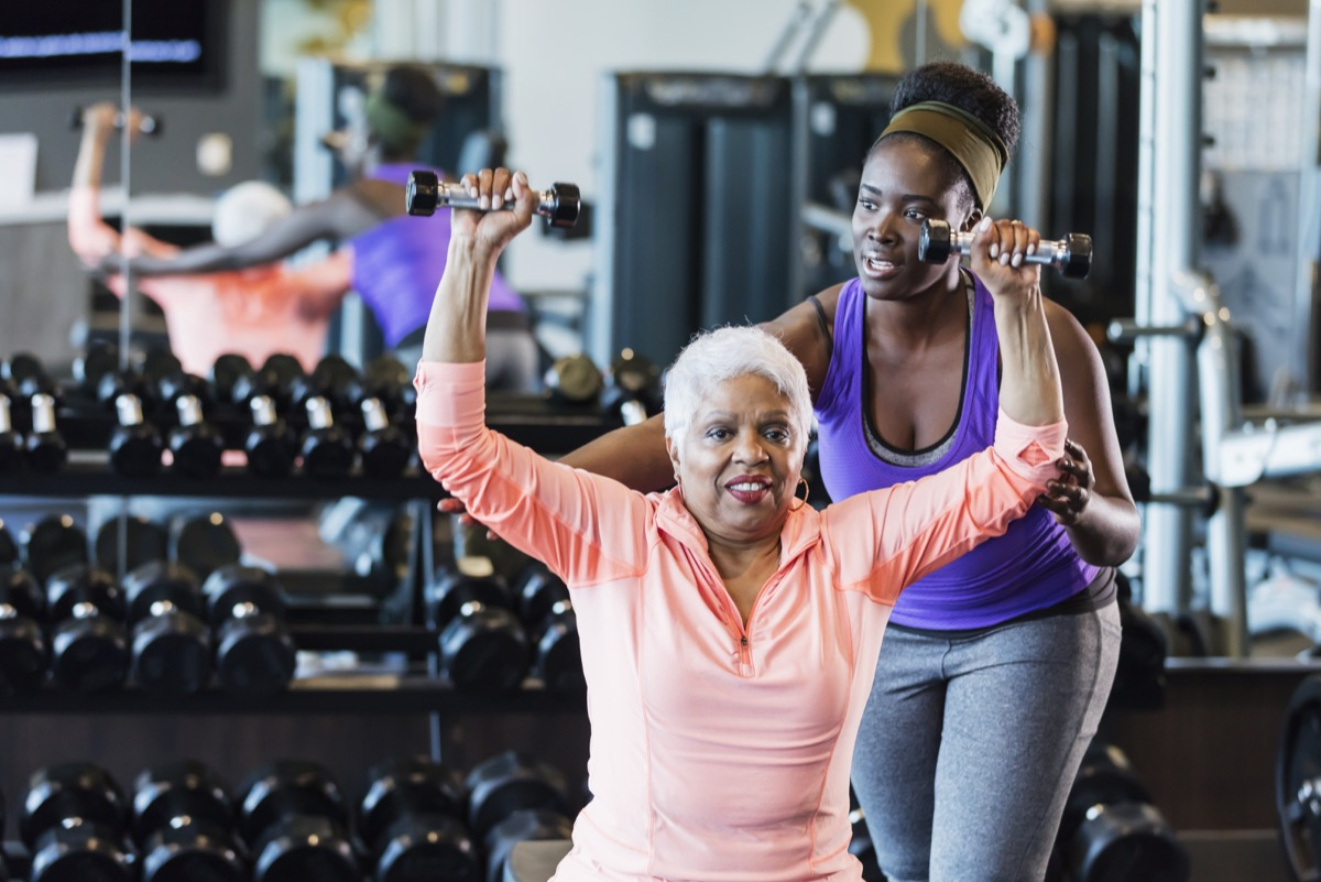 African-American fitness instructor helping senior woman